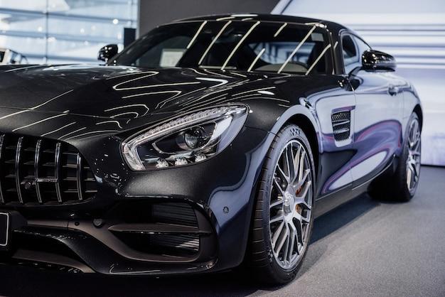 Zupełnie nowy czarny, niesamowicie polerowany, stylowy samochód zaparkowany w pomieszczeniach.