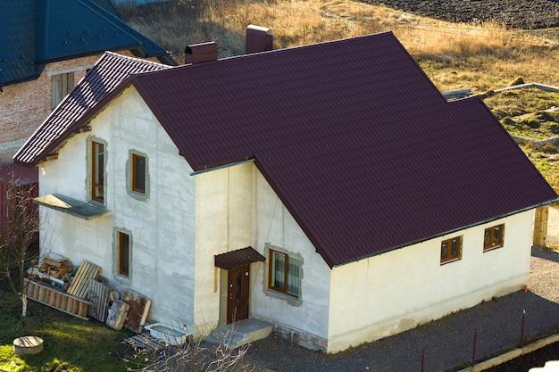 Zupełnie nowy, przestronny, otynkowany, dwupiętrowy dom jednorodzinny z brązowym dachówką i oknami czekającymi na właściciela. nieruchomości budowlane, hipoteczne i nieruchomościowe.