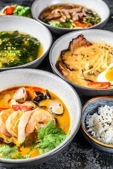 Zupy azjatyckie, miso, ramen, tom yam, pho bo. czarne tło. widok z góry