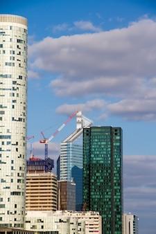 Żuraw budowlany i drapacze chmur w budowie przeciw błękitne niebo