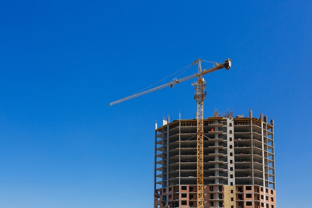 Żuraw budowlany. na tle błękitnego nieba w budowie jest wysoki budynek. przemysł budowlany i przemysł