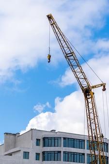 Żuraw budowlany na tle nieba w pobliżu nowego budynku