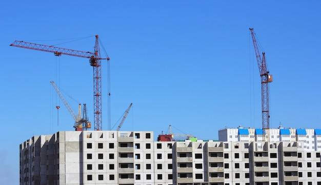 Żuraw i błękitne niebo na placu budowy