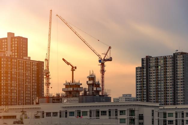 Żuraw i budowa pracuje na budynku kompleksie przy zmierzchem, rozwija miasta pojęcie