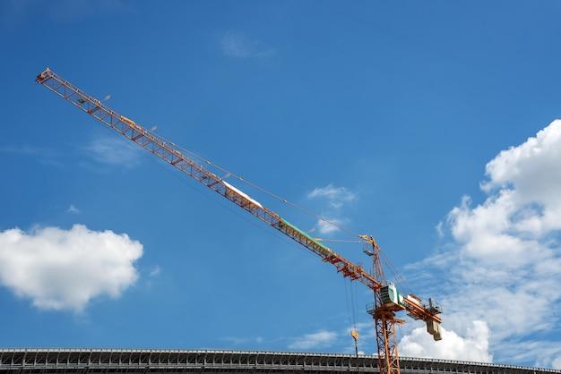 Żuraw i budowa robot budowlany i niebieskie niebo
