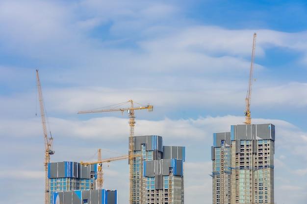 Żuraw i budynek w budowie przeciw błękitne niebo