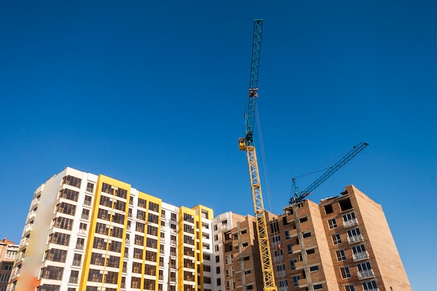 Żuraw i wysoki wzrost buduje w budowie przeciw niebieskiemu niebu. nowoczesna architektura tło