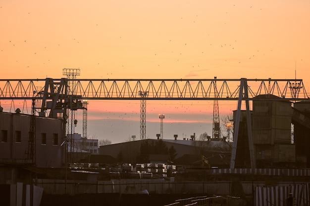Żuraw kontenerowy na tle zachodu słońca. krajobraz przemysłowy w porcie morskim.