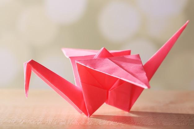 Żuraw origami na drewnianym stole, na jasnym tle