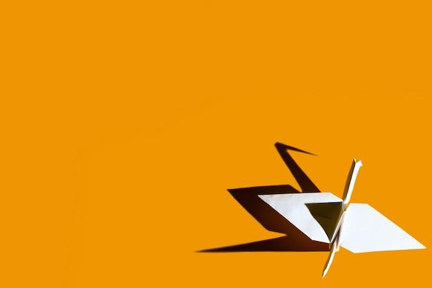Żuraw origami wykonany z papieru na jasnym żółtym tle z twardym cieniem