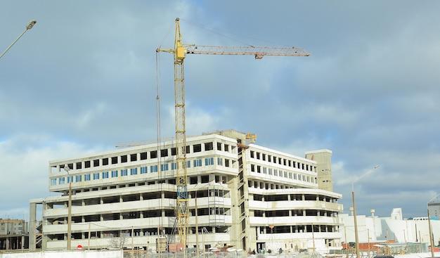 Żuraw wieżowy na budowie na tle nowego b