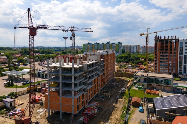 Żuraw wieżowy w wysokim betonowym budynku mieszkalnym w budowie. koncepcja rozwoju nieruchomości.