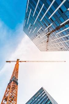 Żuraw wieżowy żółty. widok z dołu wysokiego dźwigu budowlanego obok nowoczesnego budynku.