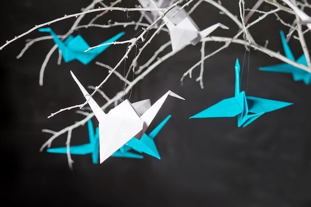 Żurawie origami na gałęziach