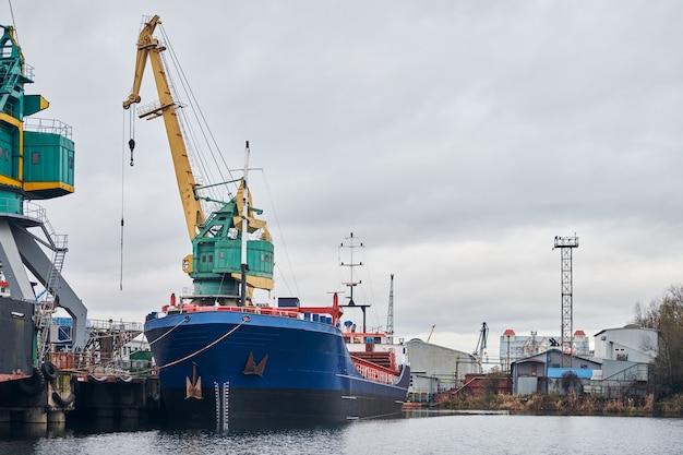 Żurawie portowe i zacumowany statek towarowy w porcie.