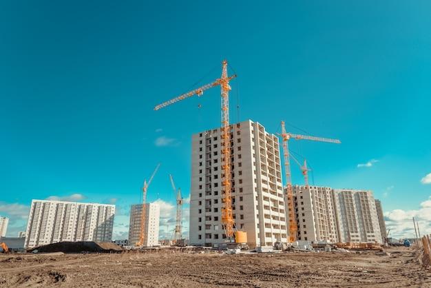 Żurawie przemysłowe i nowy budynek wielokondygnacyjny.