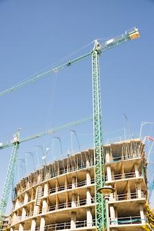 Żurawie wieżowe budujące budynek mieszkalny