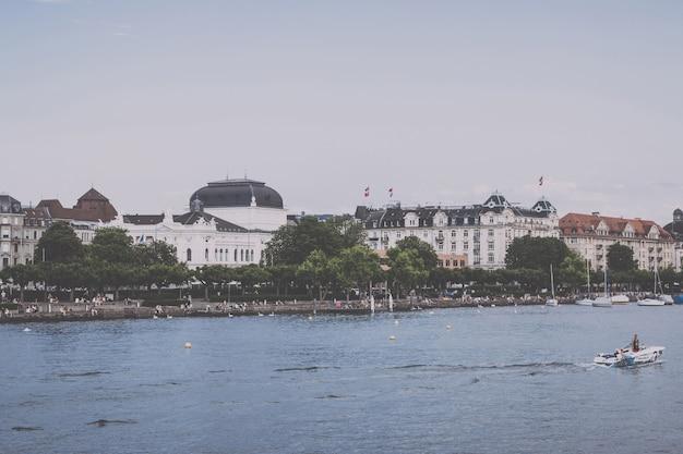 Zurych, szwajcaria - 21 czerwca 2017 r.: widok na jezioro zuryskie i operę w zabytkowym centrum miasta zurych. letni krajobraz, słoneczna pogoda, błękitne niebo i słoneczny dzień