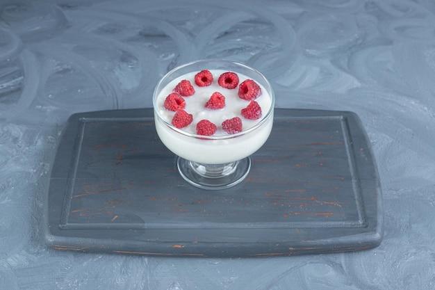 Zużyta granatowa drewniana deska pod miską puddingu ryżowego na marmurowym stole.