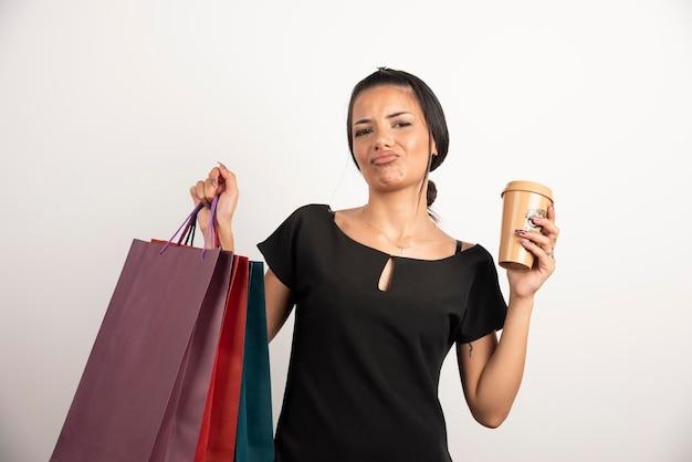 Zużyta kobieta z kawą niosąca kolorowe torby na zakupy.