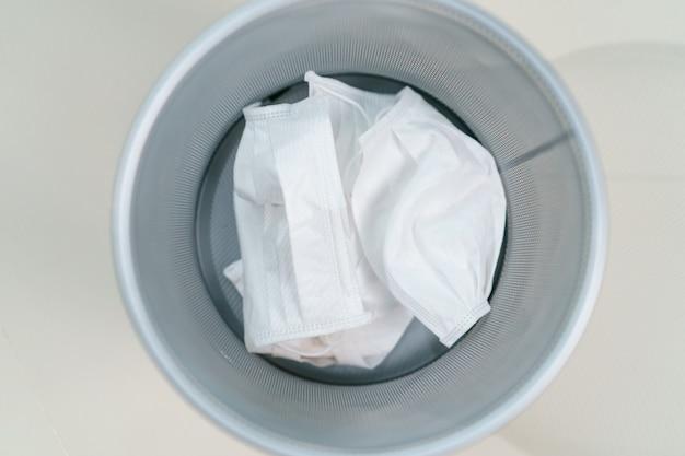 Zużyte maski na pojemniki na odpady medyczne. zapobieganie rozprzestrzenianiu się wirusa korony, covid-19.
