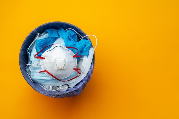 Zużyte maski zakaźne i rękawice medyczne do kosza na śmieci