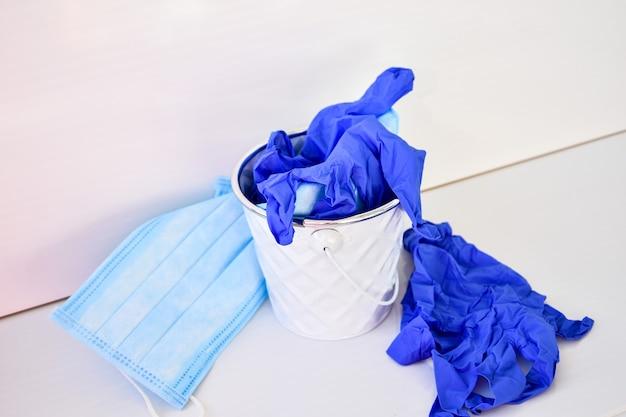 Zużyte maski zakaźne i rękawice medyczne w koszu na śmieci. śmieci koronawirusa. covid-19 odpady medyczne. używane środki ochrony osobistej ppe . zanieczyszczenie plastikiem po pandemii