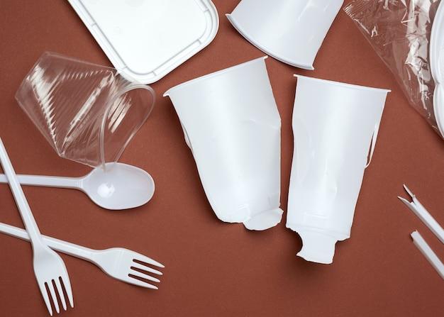 Zużyte plastikowe naczynia, kawałki plastiku i biała plastikowa torba na brązowej powierzchni