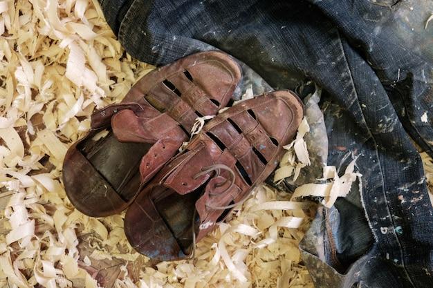 Zużyte skórzane buty i podarte dżinsy na kawałkach drewna w warsztacie malarza
