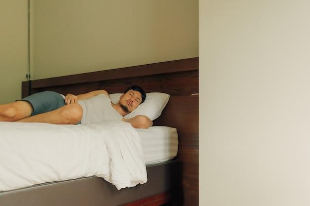 Zużyty azjata śpi na łóżku. pojęcie wyczerpania i zmęczenia.