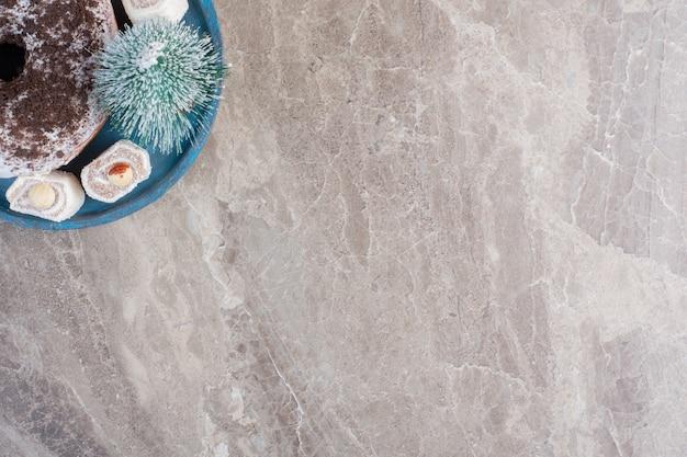 Zużyty talerz z tureckimi przysmakami, figurką drzewa i pączkiem na marmurze.