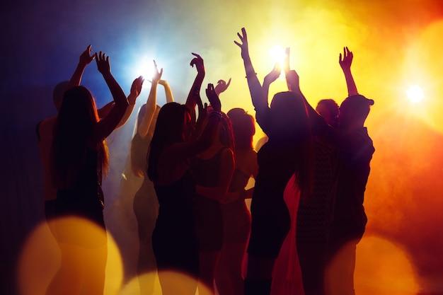 Zwariowany. tłum ludzi w sylwetce podnosi ręce na parkiecie na neonowym tle. życie nocne, klub, muzyka, taniec, ruch, młodzież. żółto-niebieskie kolory i poruszające dziewczyny i chłopcy.