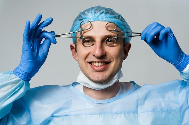 Zwariowany uśmiechnięty lekarz chirurg z szalonymi emocjami