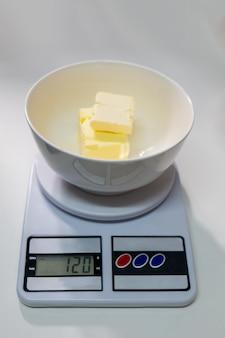 Zważ masło, aby uzyskać doskonałość przepisu na chleb.