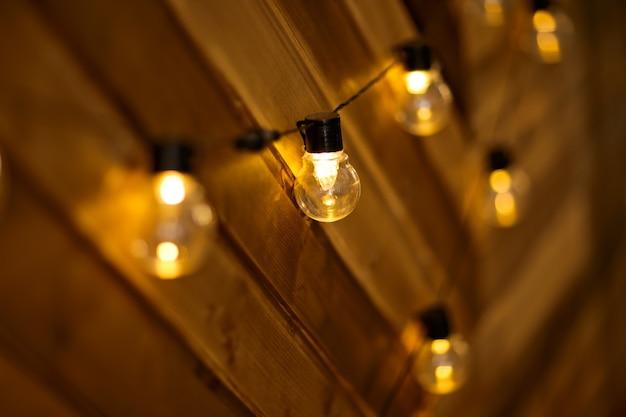 Zważ żarówki na drewnianej ścianie. płonące girlandy garland na drewnianym tle. żarówki na drewnianym tle.