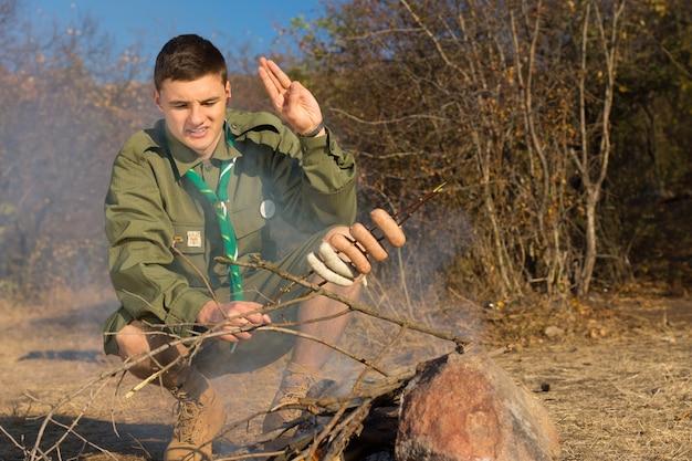 Zwiadowca pozdrawiający swoje kiełbaski do gotowania, gdy pochyla się nad małym ogniskiem na polanie z niegotowanymi kiełbaskami nadzianymi na gałązkę