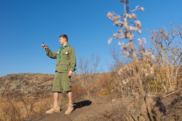 Zwiadowca stojący na skale odczytujący kompas, aby ustalić swoją lokalizację i określić kierunek swojej trasy