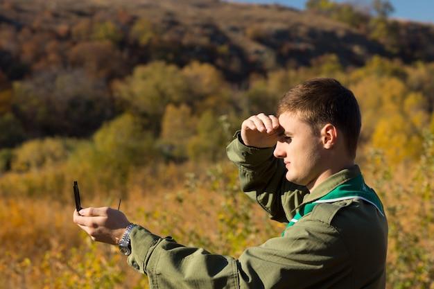 Zwiadowca zasłania ręką oczy przed słońcem, gdy odczytuje swój kompas magnetyczny, aby znaleźć swoją lokalizację i kierunek podróży