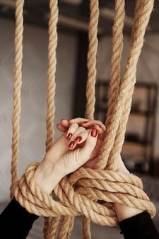 Związany liną kobiece ręce. piękne dłonie z czerwonymi paznokciami. pojęcie seksu lub przemocy