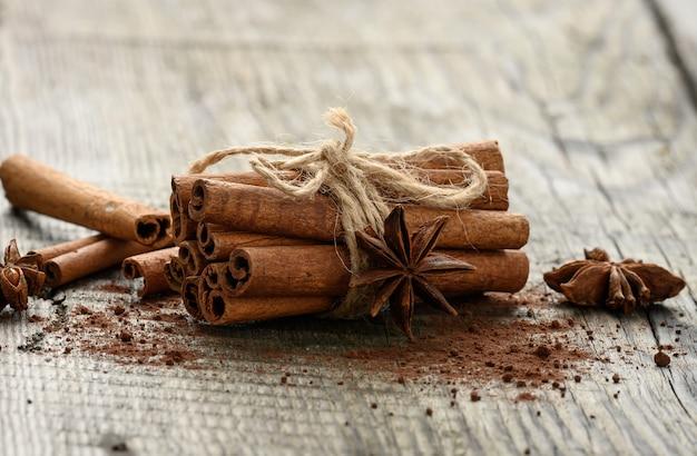 Związany pęczek brązowych laski cynamonu na szarym drewnianym tle, z bliska
