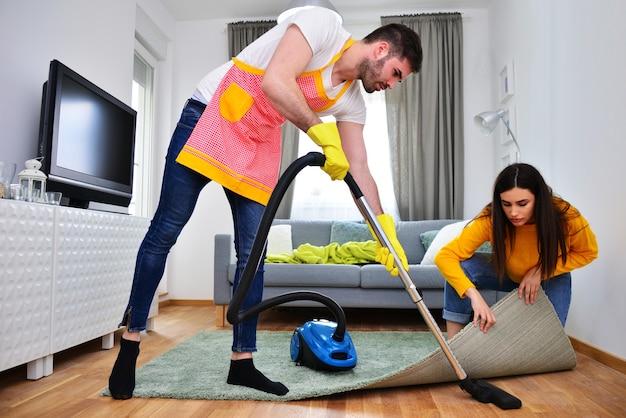 Związek, życie małżeńskie, prace i obowiązki domowe, koncepcja równości płci. mężczyzna sprzątający, podczas gdy kobieta mu pomaga.
