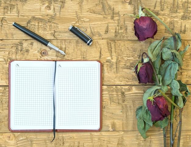 Zwiędłe róże z notatnikiem i wiecznym piórem na rustykalnym stole.