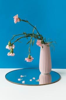 Zwiędły różowy goździk w różowym wazonie na błyszczącej tacy