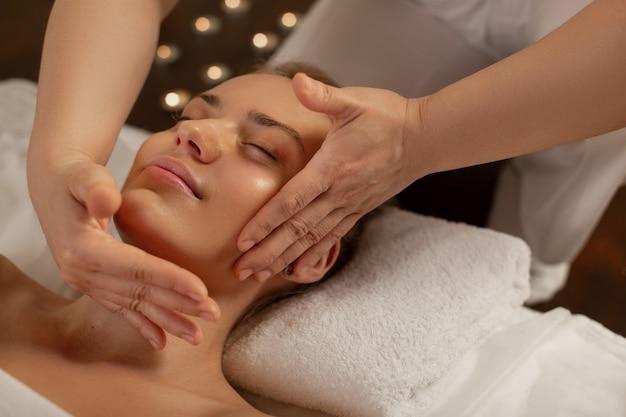 Zwiedzanie profesjonalnego centrum. dokładna mistrzyni masażu z wykwalifikowanymi dłońmi delikatnie dotykającymi twarzy jej promiennego klienta