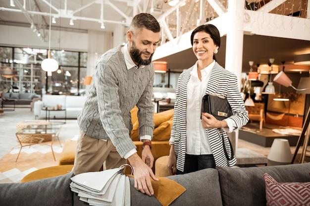 Zwiedzanie specjalistycznego sklepu. brunetka, przystojny kobieta z szerokim uśmiechem torba do przenoszenia, podczas gdy jej mąż pokazuje przykłady