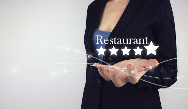 Zwiększ ocenę koncepcji firmy. ręka trzymać cyfrowy hologram pięć gwiazdek i napis restauracja na szarym tle. najlepsze doskonałe usługi
