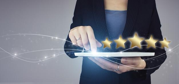 Zwiększ ocenę lub ranking, ocenę i pomysł na klasyfikację. biała tabletka w ręku businesswoman z cyfrowym hologramem pięć gwiazdek 5 znak oceny na szarym tle. recenzja, ocena, satysfakcja.