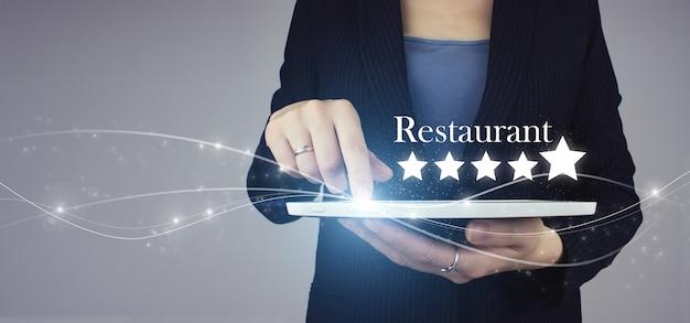 Zwiększ ocenę lub ranking, ocenę i pomysł na klasyfikację. biała tabletka w ręku z cyfrowym hologramem pięć gwiazdek i tekst restauracja na szaro. ręka wskazująca pięciogwiazdkową firmę ratingową.