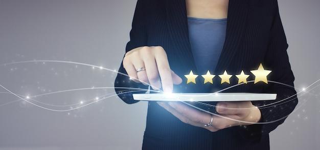 Zwiększenie oceny oceny i koncepcji klasyfikacji. biała tabletka w ręku businesswoman z cyfrowym hologramem pięć gwiazdek 5 znak oceny na szarym tle. recenzja, ocena, satysfakcja.
