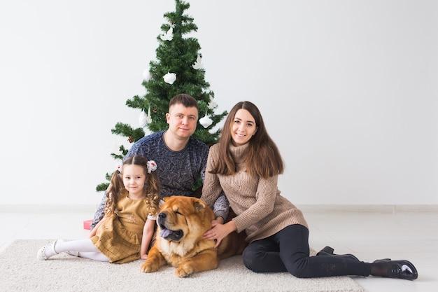 Zwierzę, święta i świąteczna koncepcja - rodzina z psem siedzą na podłodze w pobliżu choinki.